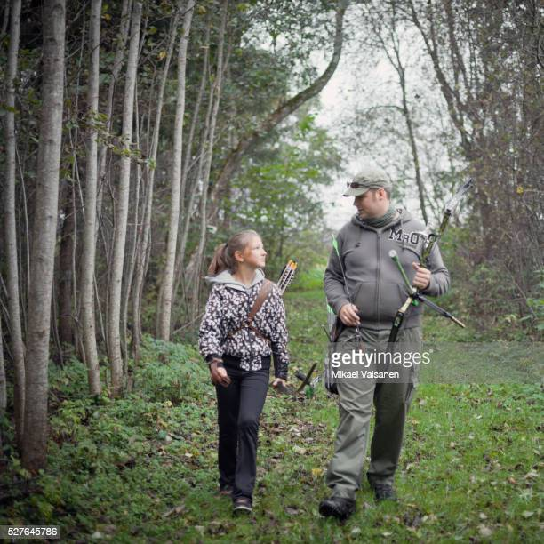 Father and daughter (10-12) walking in shooting range with bow and arrow