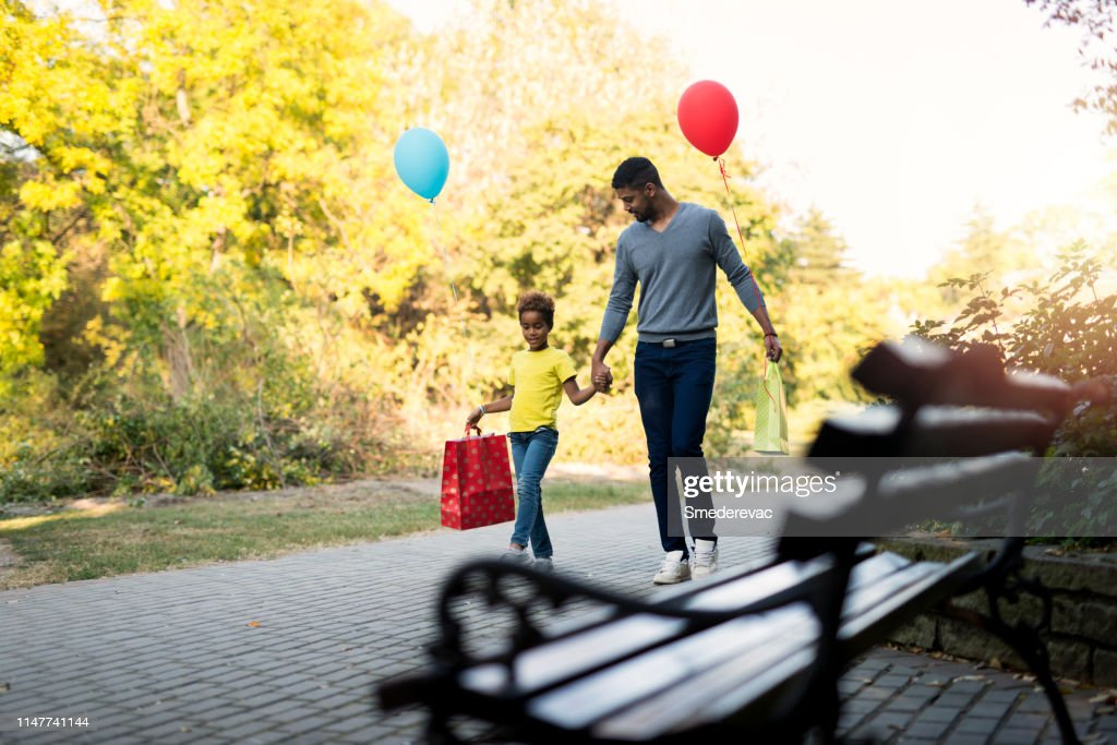Father and daughter walking in the park after shopping holding hands together. : Stock Photo