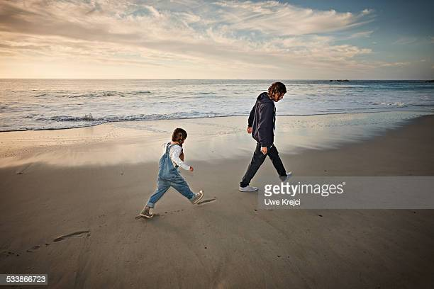 father and daughter walking on beach - following stock pictures, royalty-free photos & images