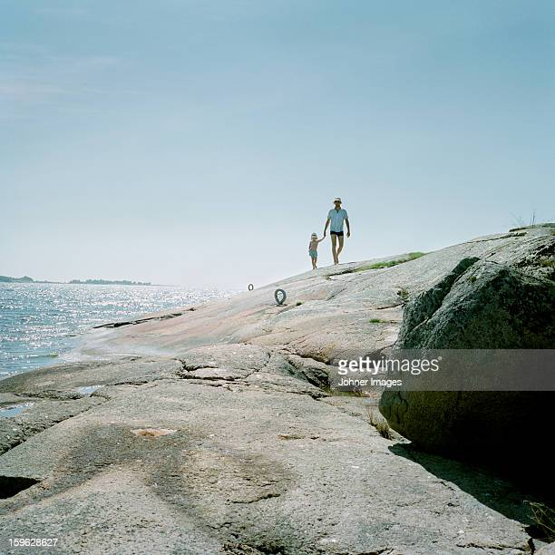 father and daughter walking on cliffs, blekinge, sweden. - archipelago stock pictures, royalty-free photos & images