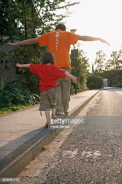 Father and daughter walking on curb