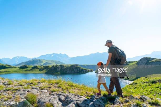 father and daughter walking on meadow during sunny day - france stock pictures, royalty-free photos & images