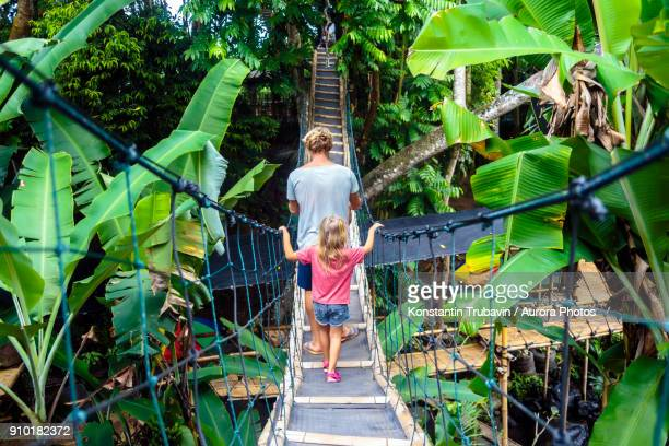 Father and daughter walking on rope bridge in forest town, Bali, Indonesia