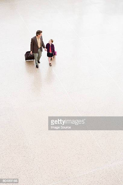A father and daughter walking through an airport