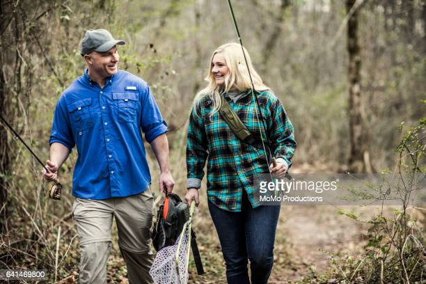 Father and daughter walking through woods with fishing rods