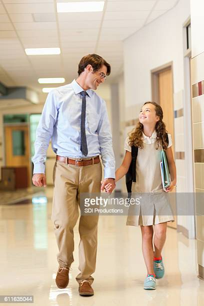 Father and daughter walking together to elementary school classroom