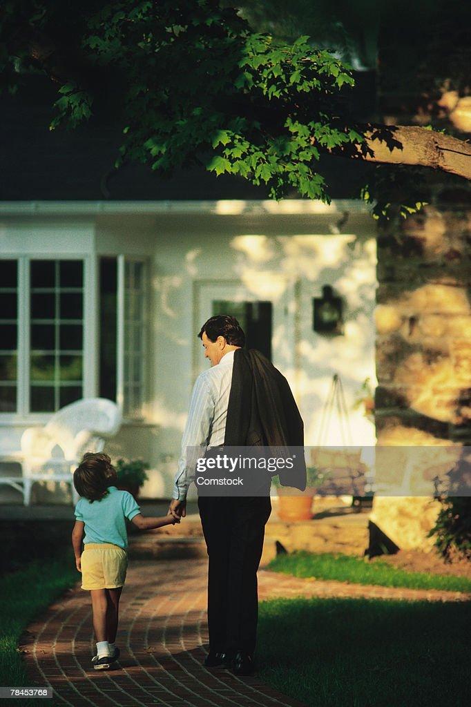 Father and daughter walking toward front door : Stockfoto