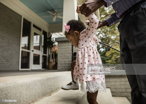 father and daughter (18 months) walking up steps to house - affectionate stock pictures, royalty-free photos & images