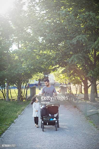 father and daughter walking with baby stroller on footpath against trees - family with one child stock pictures, royalty-free photos & images