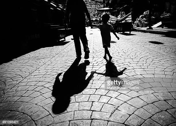 Father And Daughter Walking With Shadow On Street