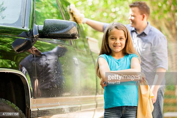 Father and daughter wash the family car together outdoors.