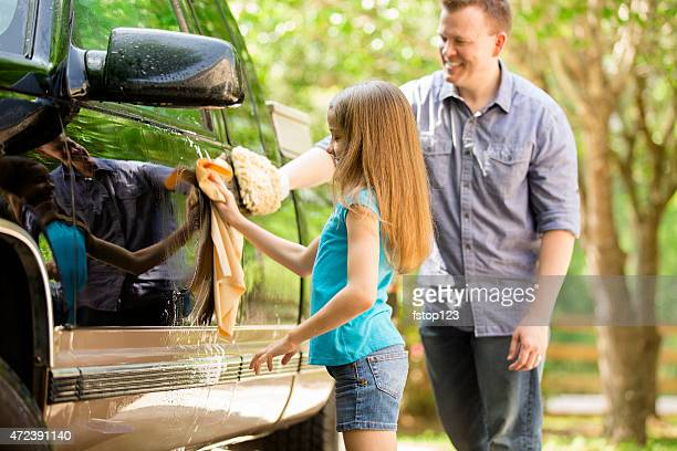 Father and daughter wash the family vehicle together outdoors.