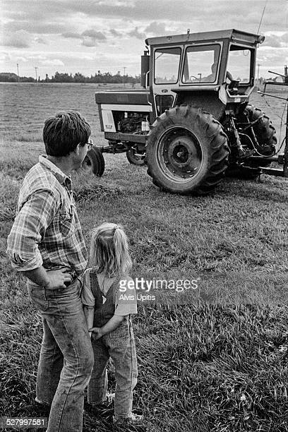 father and daughter watch son work tractor - filme de arquivo - fotografias e filmes do acervo