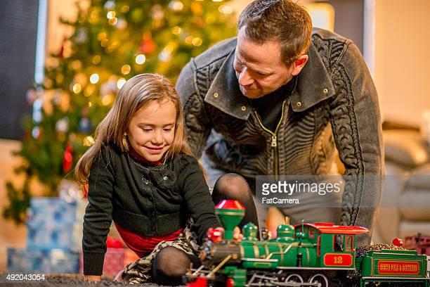 Pai e filha a olhar para um brinquedo de comboio