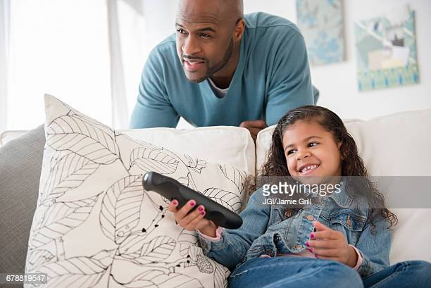 Father and daughter watching television on sofa,