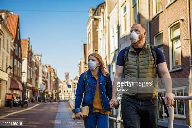 vader en dochter die gezichtsmaskers in het centrum van een stad dragen - zuid holland stockfoto's en -beelden