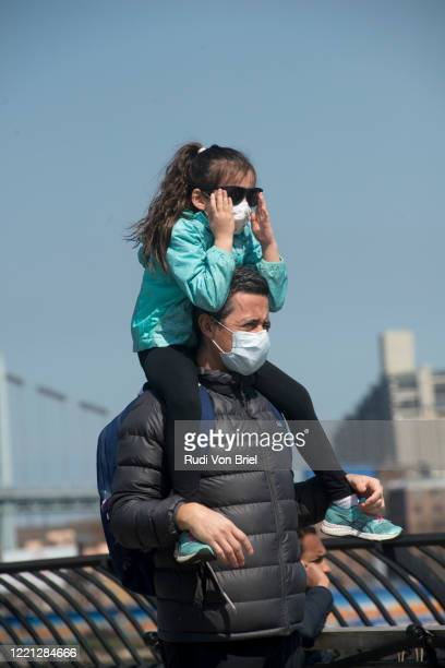 a father and daughter wearing masks in response to covid-19 in carl schurz park on the upper east side in new york city. - pathogen transmission stock pictures, royalty-free photos & images