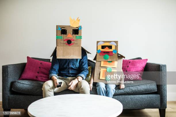 father and daughter wearing robot costumes watching television - genderblend stock pictures, royalty-free photos & images