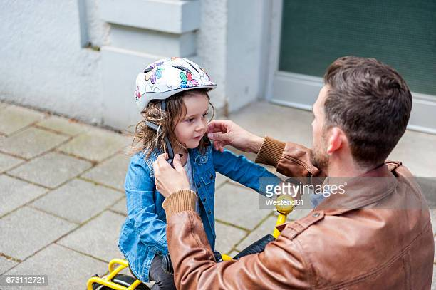 father and daughter with bicycle helmet - sportschutzhelm stock-fotos und bilder