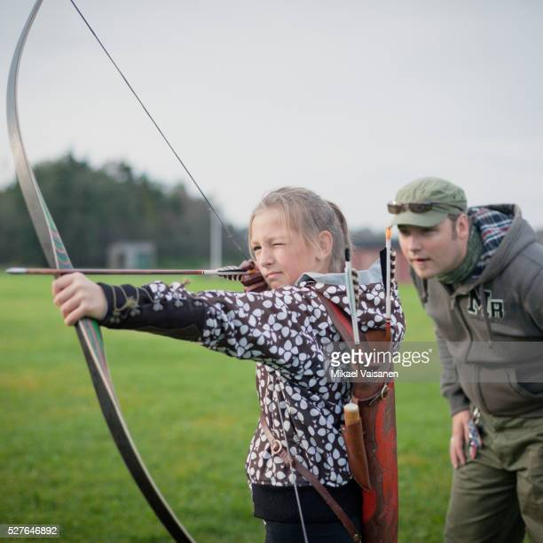 Father and daughter (10-12) with bow and arrow