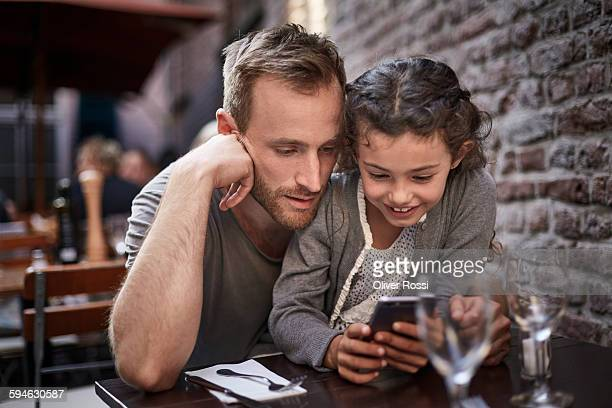 Father and daughter with cell phone in restaurant
