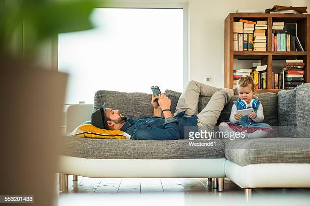 Father and daughter with digital tablet and smartphone on sofa