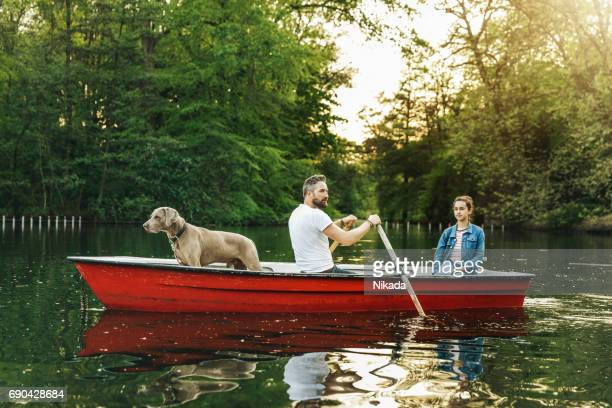 father and daughter with dog in rowboat on lake - rowing boat stock pictures, royalty-free photos & images