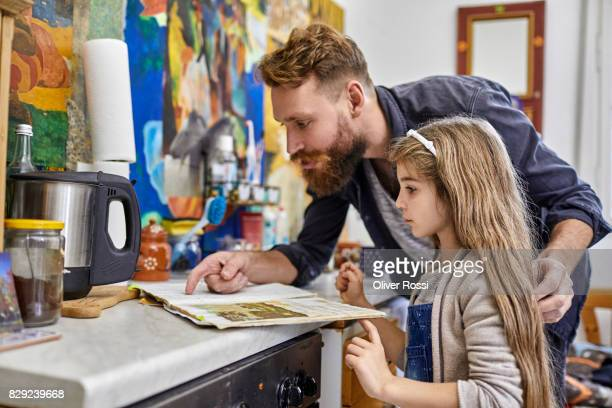 Father and daughter with old-fashioned book in kitchen