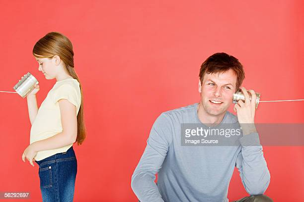 Father and daughter with tin can phone