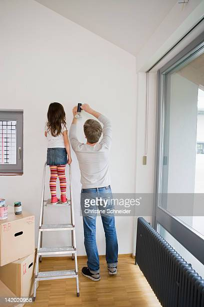 Father and daughter working in new house
