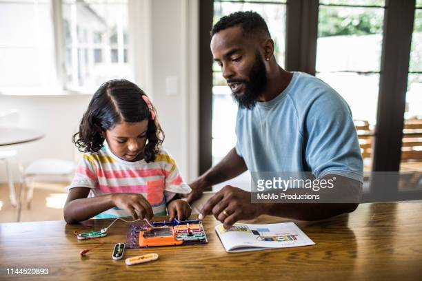 father and daughter working on science project at home - home schooling stock pictures, royalty-free photos & images