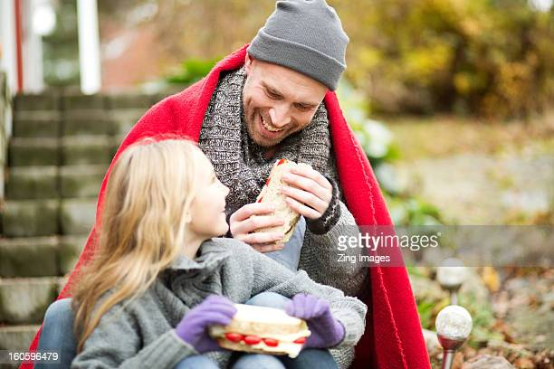 Father and daughter wrapped in blanket outdoors