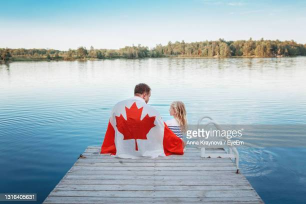 father and daughter wrapped in canadian flag sitting on pier by lake. canada day celebration outdoor - canada day stock pictures, royalty-free photos & images