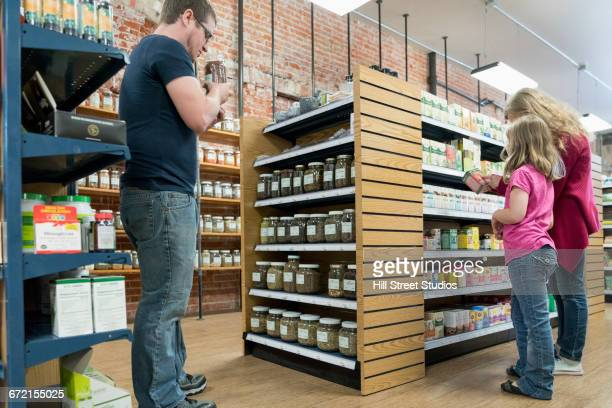 Father and daughters browsing in nutrition store