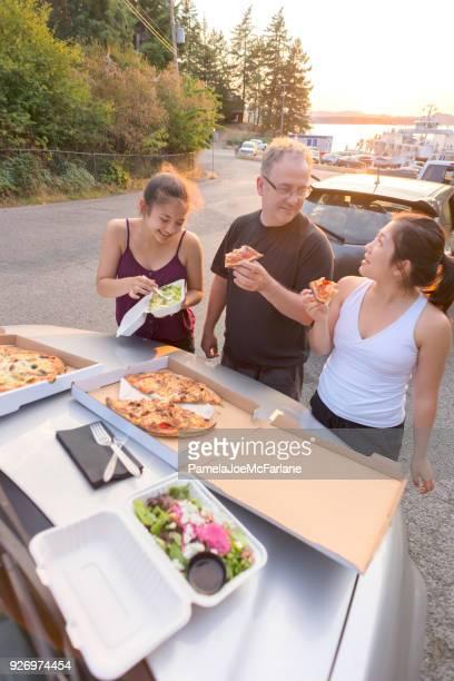 Padre e hijas comiendo Pizza y ensalada, a la espera de Ferry