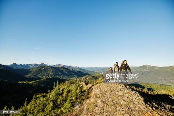 father and daughters hiking on rocky ridge during backpacking trip - journey stock pictures, royalty-free photos & images
