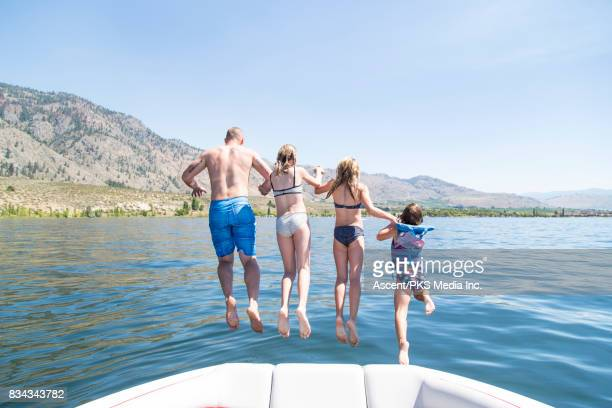 Father and daughters jump from boat together, lake