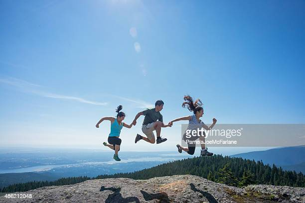 Father and Daughters Jumping on Mountain Top, Holding Hands