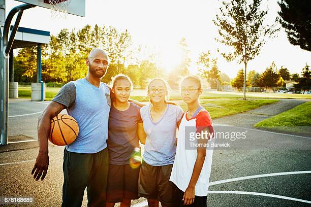 Father and daughters on outdoor basketball court