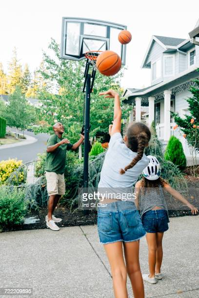 Father and daughters playing basketball in driveway