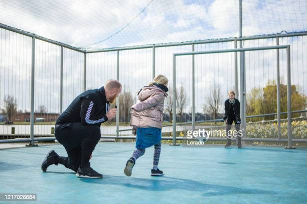 father and daughters playing football outdoors - team sport stock pictures, royalty-free photos & images