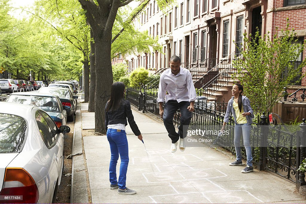 Father and daughters playing jump-rope : Stock Photo