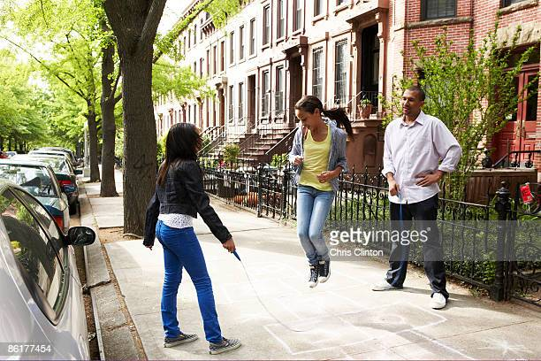 father and daughters playing jump-rope - terraced_house stock pictures, royalty-free photos & images