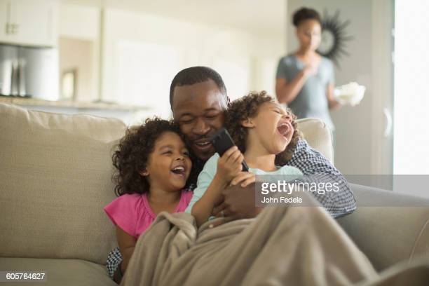 father and daughters playing on sofa - family watching tv stock pictures, royalty-free photos & images