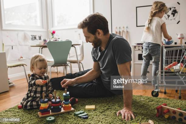 Father and daughters playing with toys in playroom at home
