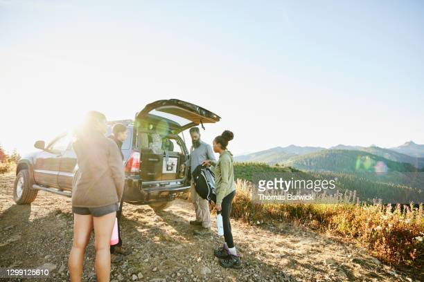 father and daughters preparing to begin backpacking trip at back of car - boot stock pictures, royalty-free photos & images