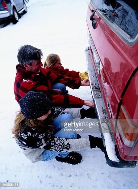 Father and Daughters Pulling a Car Stuck in Snow