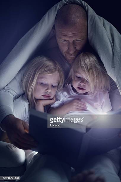 father and daughters reading a book at bedtime - daughters of darkness stock pictures, royalty-free photos & images