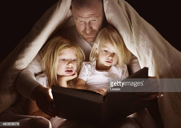 father and daughters reading book at bedtime - fairytale stock pictures, royalty-free photos & images