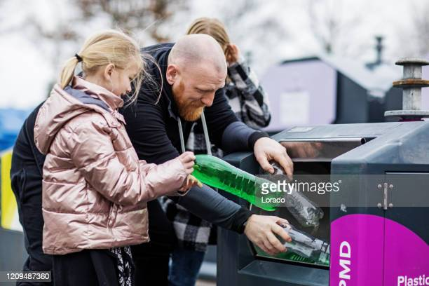 father and daughters recycling plastic bottles - consumerism stock pictures, royalty-free photos & images
